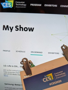 Photo of a 2020 CES badge held in front of a screen showing a schedule of on-demand videos from CES 2021