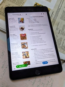 Photo of an iPad open to Evernote, showing a list of recipes. Below it sits my recipe binder, showing a handwritten recipe from my mom.