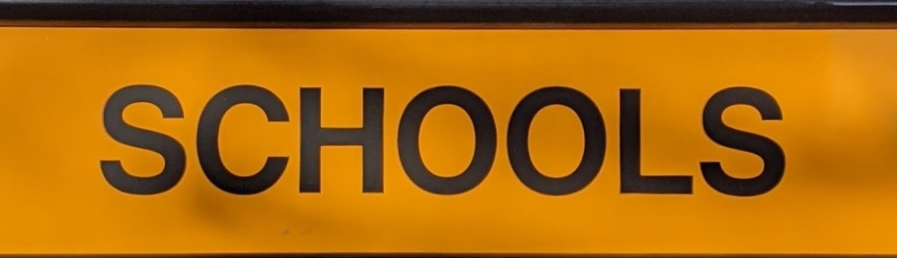 """Picture of a side of a school bus, showing the word """"Schools"""""""