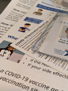 Photo showing part of my Virginia MRC badge and COVID-19 vaccination card atop papers relating post-vaccination advice.