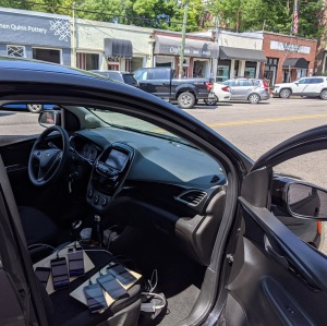 Photo shows my rental car with the door open, six test phones sitting on the passenger seat, and a row of storefronts in the Little Five Points neighborhood of Raleigh.