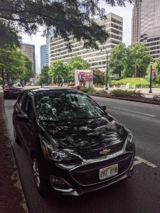 Photo shows a black Chevy Spark with Hawaii plates, with the High Museum of Art across the street and midtown Atlanta buildings in the background