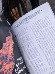 Photo of first two pages of the story, held in front of a loop of fiber-optic cable hanging off a utility pole.