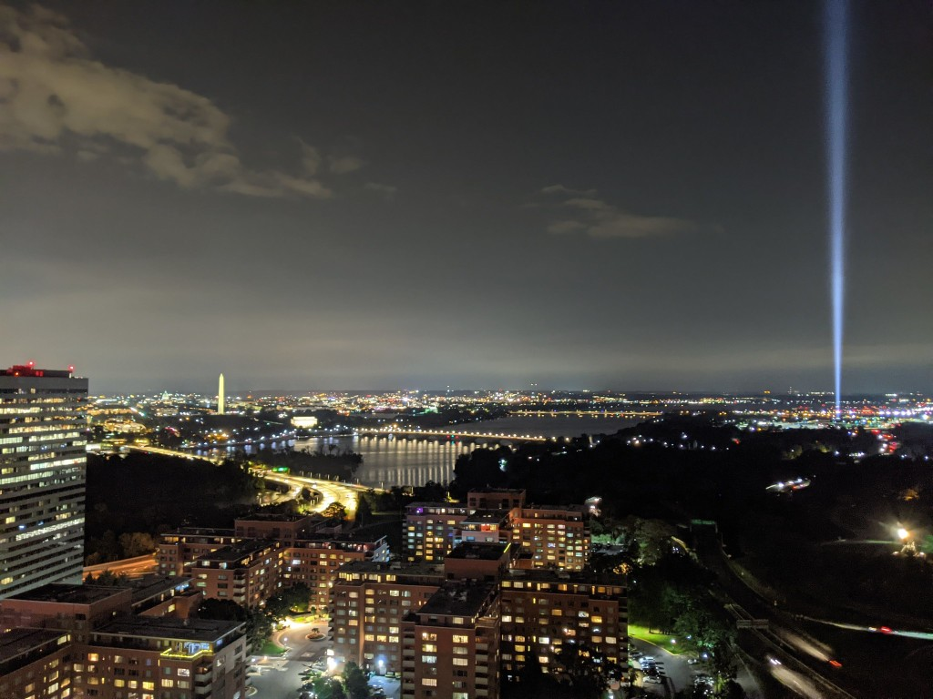 """Photo taken from a Rosslyn rooftop Sept. 8 shows the """"tower of light"""" tribute shining into the night sky from the Pentagon, with the river, Memorial Bridge and the Washington Monument to its left."""
