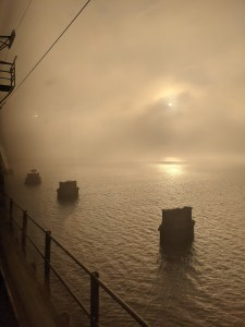Photo shows the footings of the footings railroad bridge in the Susquehanna River as seen from the current bridge, with the sun obscured by fog and part of the overhead catenary visible.